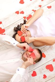 La saint-valentin, un couple amoureux gît parmi les cœurs sur le sol les yeux fermés avec des cœurs