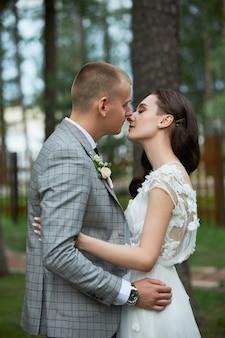 Saint valentin, un couple amoureux s'embrassant et s'embrassant dans le parc. l'homme embrasse la belle femme, fiançailles