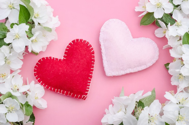 Saint valentin, deux coeurs sur fond rose avec des fleurs de pomme