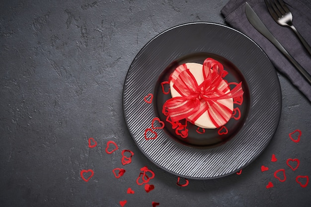 Saint valentin ou dîner romantique. assiette noire vide et boîte avec un cadeau. serveur festif