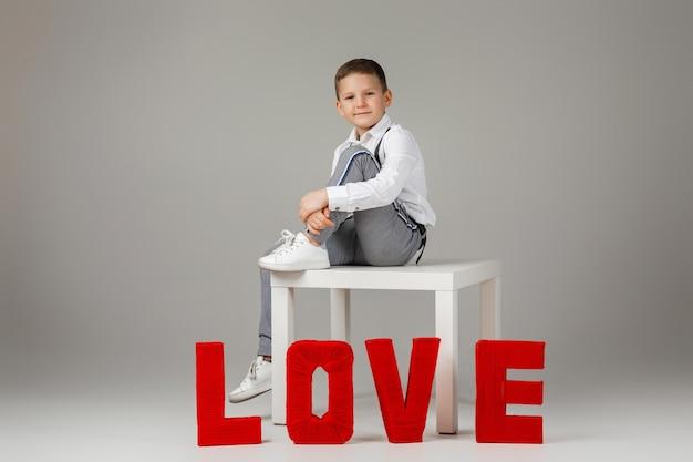 La saint-valentin. élégant garçon enfant assis près de lettres de mot rouge love sur fond gris studio