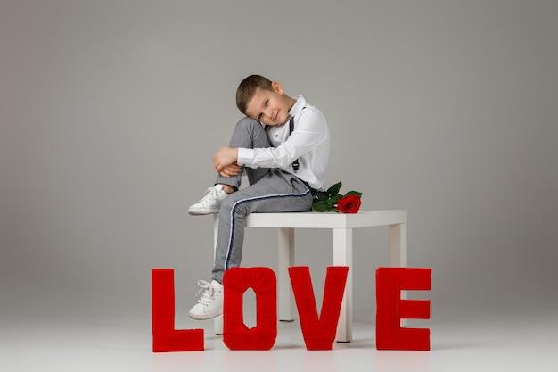 La saint-valentin. garçon enfant élégant avec rose rouge assis près de lettres de mot rouge love sur fond gris studio