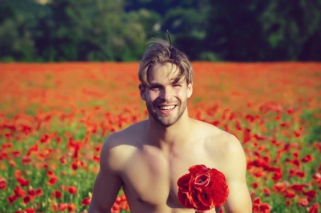 La saint-valentin. heureux homme nu avec bouquet. mec musclé souriant dans le champ de pavot rouge, printemps
