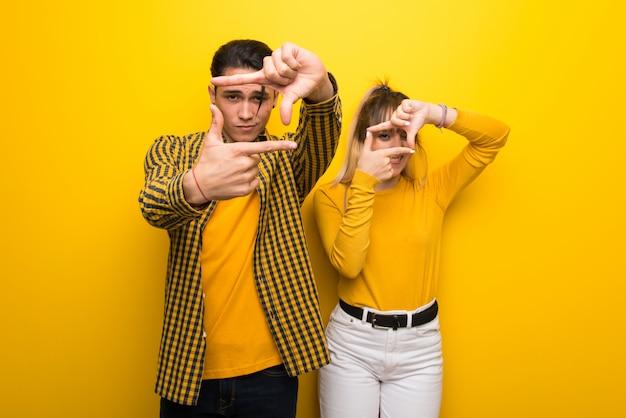 En saint valentin jeune couple sur fond jaune vif se concentrant sur le visage. symbole d'encadrement