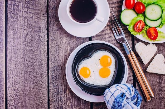 La saint valentin. œufs brouillés en forme de cœur, café noir et assiette de légumes
