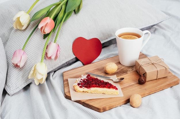La saint-valentin. petit déjeuner au lit, fleurs et cadeau.