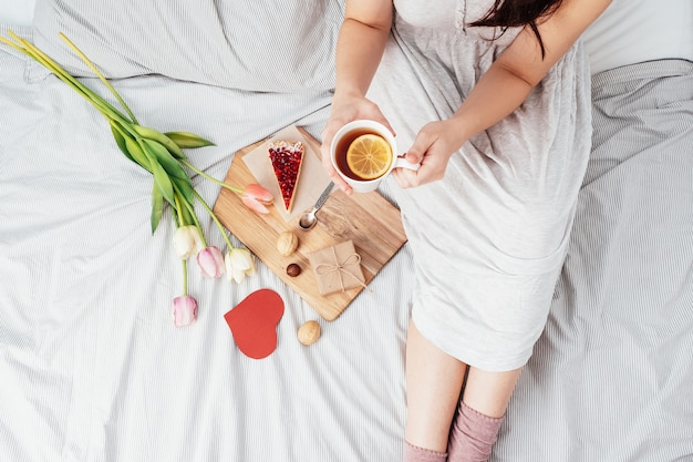 La saint-valentin. petit-déjeuner, un cadeau et des fleurs pour la fille que vous aimez. fille au lit avec des fleurs le 14 février.