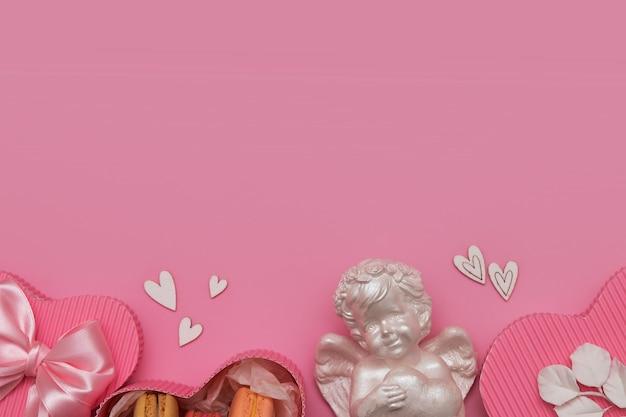 La saint-valentin à plat avec boîte-cadeau, macaron, arc, ange, coeurs sur fond rose avec espace copie