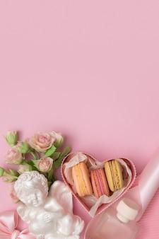 La saint-valentin à plat avec boîte-cadeau, macaron, fleurs arc, ange sur fond rose avec espace copie