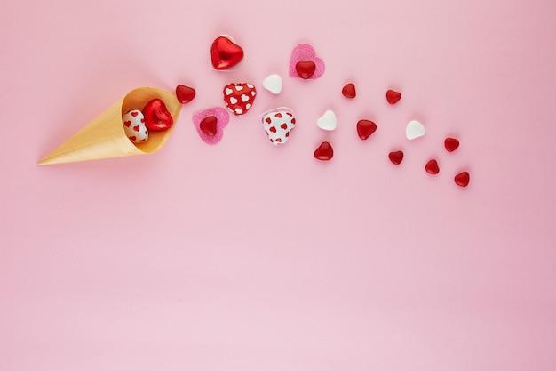 La saint-valentin à plat avec des coeurs de bonbons volant hors d'un cornet de crème glacée sur rose