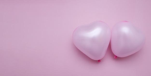 La saint-valentin à plat poser avec deux ballons en forme de coeur bannière espace copie rose monochrome
