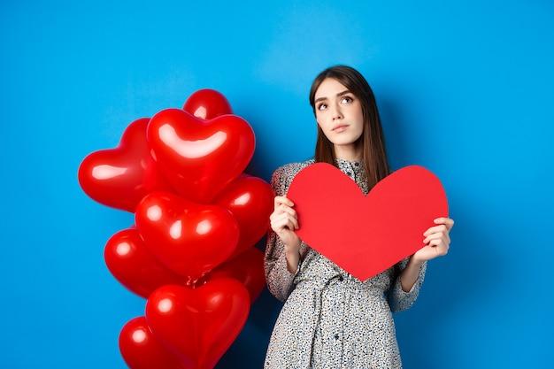 Saint valentin rêveuse jolie dame en robe tenant une grande découpe de coeur rouge et à la recherche du véritable amour ...