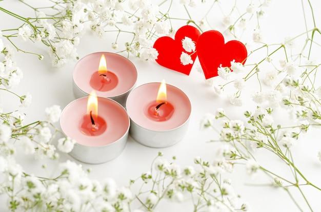 Saint valentin romantique. bougies allumées et coeurs rouges décorés de fleurs sur blanc.