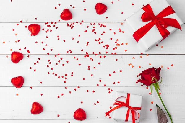 La saint valentin. roses rouges et coffret cadeau sur table en bois