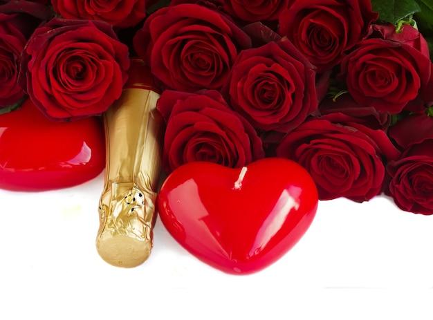 Saint-valentin roses rouges sombres avec des bougies coeurs et vin champagne isolé