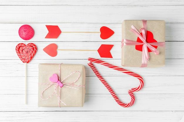 Saint valentin sertie de bonbons, boîte-cadeau et papier découpé coeur sur un fond en bois blanc, vue de dessus à plat