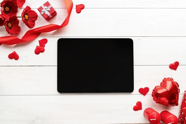 La saint-valentin. tablette avec écran noir avec des décorations de la saint-valentin, des bougies, des ballons et des confettis vue de dessus sur fond en bois blanc