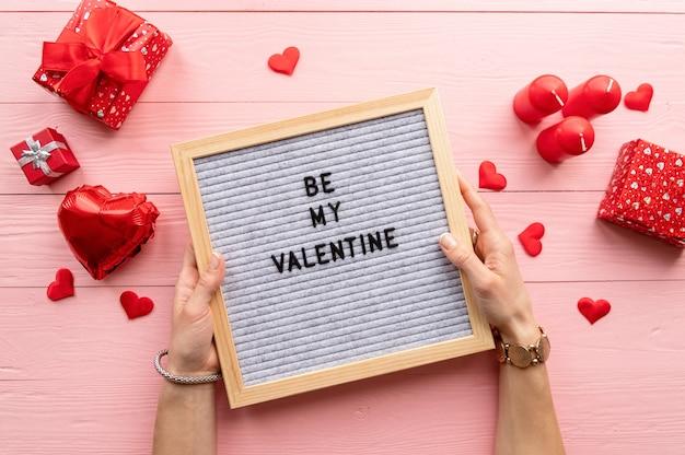 La saint-valentin. vue de dessus des mains féminines tenant une lettre en feutre boead avec texte be my valentine sur fond de bois rose
