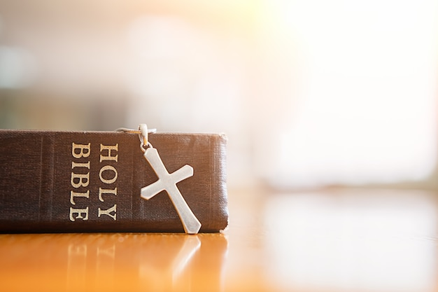 Sainte bible et croix sur table.