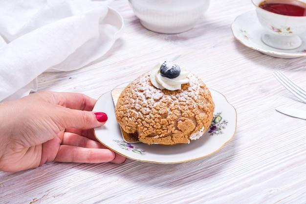 Saisir à la main un morceau de gâteau aux baies décoré de baies fraîches et d'une tasse de thé sur fond de bois