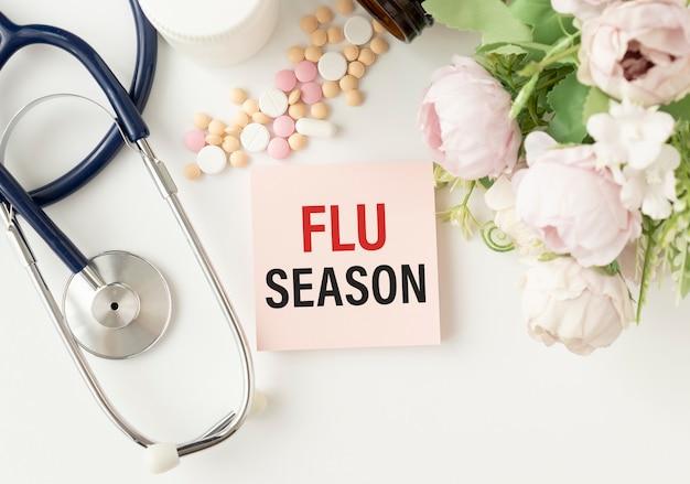 Saison de la grippe écrite sur un papier sur la table, vue du dessus