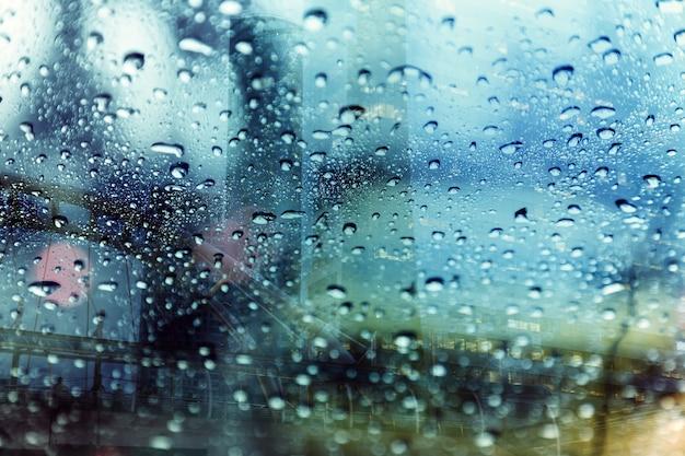 Saison de pluie avec baisse de l'eau sur la fenêtre de voiture sur la rue