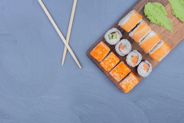 Sake maki et philadelphia rolls avec sauce wasabi sur un plateau en bois