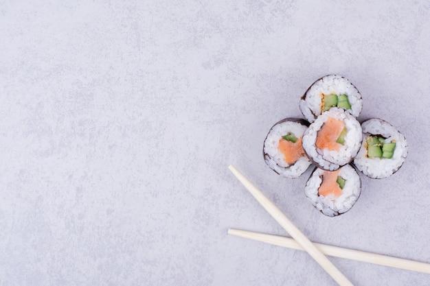 Sake maki roule au saumon et à l'avocat sur fond gris.