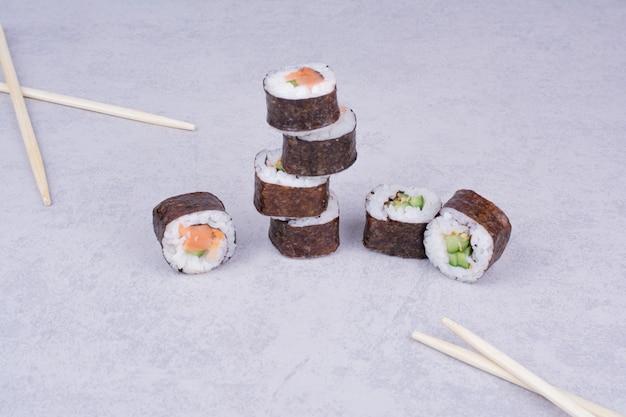 Saké maki roule sur fond gris avec des baguettes