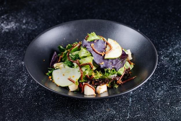 Sala léger aux ingrédients mélangés avec des herbes et du fromage.