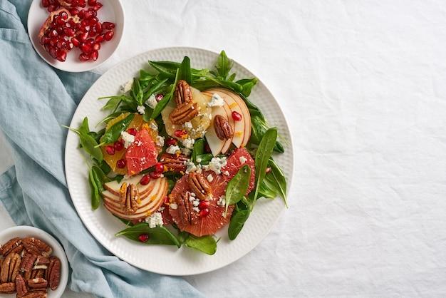 Salade d'agrumes de fruits aux noix, feuilles de laitue verte. nourriture équilibrée. épinards à l'orange, pamplemousse, pommes, pacanes et gorgonzola, garni de graines de grenade, vue du dessus, espace copie