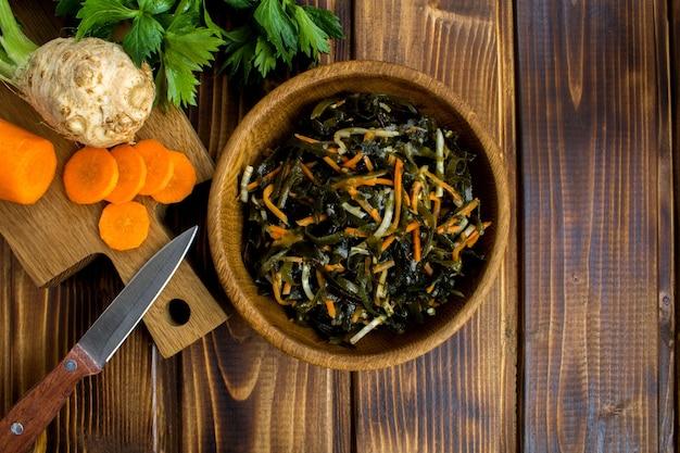 Salade d'algues, céleri et carottes dans le bol brun sur la table en bois.copier l'espace.vue de dessus.