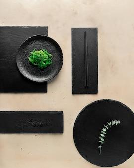 Salade d'algues chuka, graines de sésame noir, assiettes en ardoise noire de différentes formes