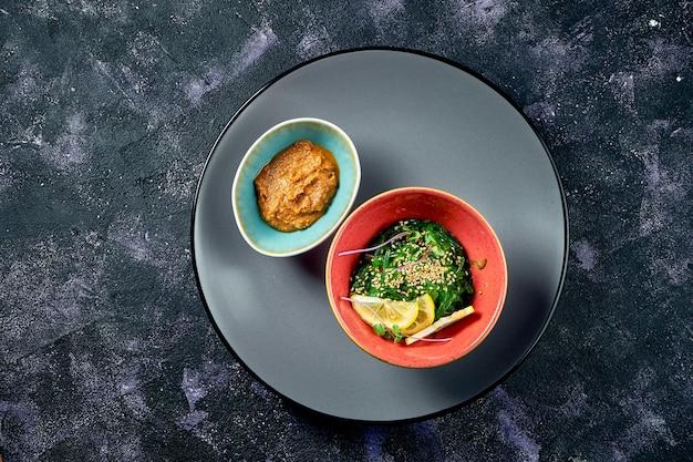 Salade d'algues wakame saines avec sauce aux arachides sur fond noir. fermer