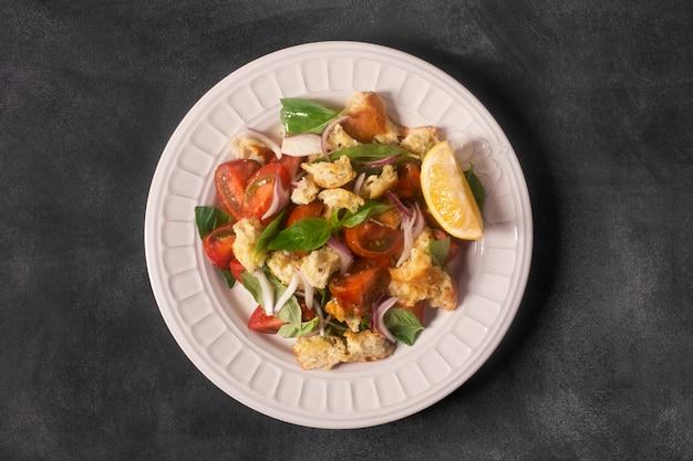 Salade apéritive italienne avec tomates, pain et bazil