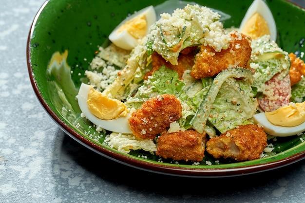 Salade appétissante au poulet pané et frit, parmesan, œuf, laitue et sauce blanche dans une assiette verte sur fond bleu