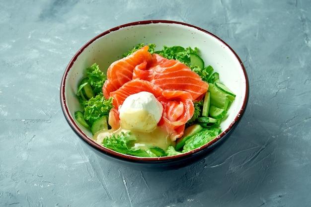 Salade appétissante au saumon, œuf poché, sauce hollandaise et laitue dans un bol blanc sur fond gris