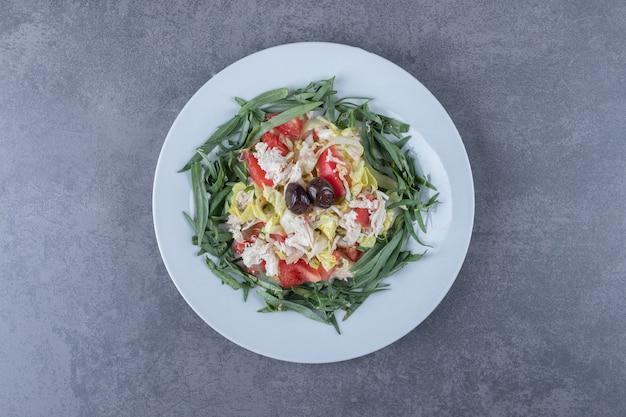 Salade appétissante fraîche sur plaque blanche.