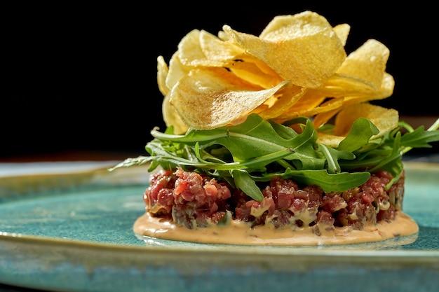 Salade appétissante - tartare de veau avec sauce, roquette, chips de pommes de terre dans une assiette bleue sur fond bleu