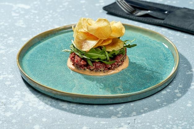 Salade appétissante - tartare de veau avec sauce, roquette, chips de pommes de terre dans une assiette bleue sur une surface bleue