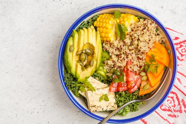Salade arc-en-ciel végétalien saine, bol à bouddha avec quinoa, tofu, avocat et chou frisé, espace de copie. concept de restauration saine