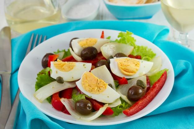 Salade sur assiette blanche et verre de vin blanc