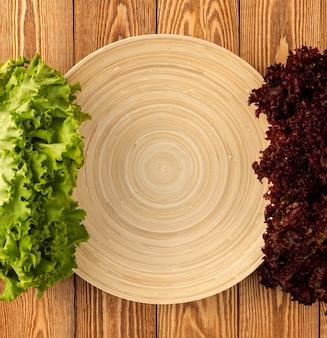 Salade et assiette vide sur un fond en bois