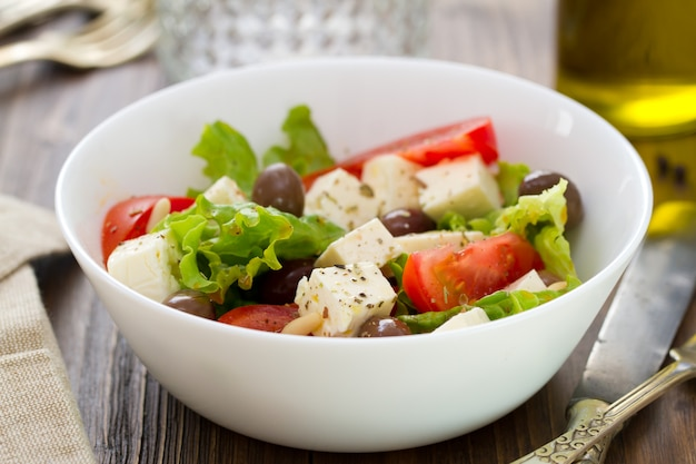 Salade au fromage avec des légumes dans un bol blanc sur fond marron