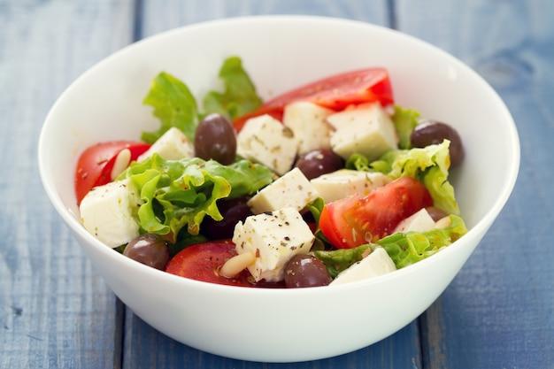 Salade au fromage avec des légumes dans un plat blanc sur fond bleu