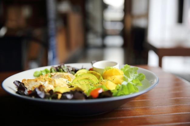 Salade au poulet avocat et mangue sur fond de bois