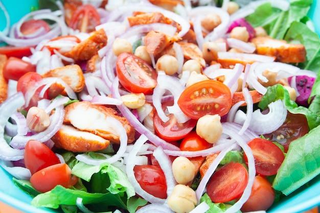 Salade au poulet grillé, tomates cerises, salade de maïs, pois chiches, laitue fraîche et oignons.