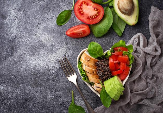 Salade au poulet, quinoa noir, tomates et avocat sur le bol en forme de coeur. équilibre sain