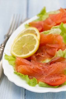 Salade au saumon sur un plat blanc sur bois bleu