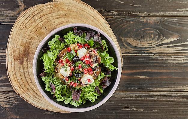 Salade d'aubergines avec fromage feta, grenade et groseilles dans une marinade au café. cuisine gastronomique française. mise à plat